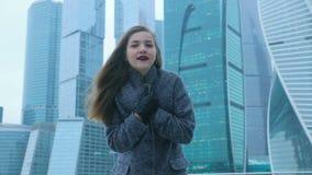 Meisje het stellen tegen de achtergrond van een wolkenkrabber stock videobeelden
