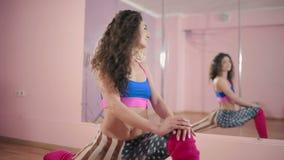 Meisje het uitrekken zich in de dansstudio dichtbij de spiegel stock video