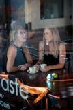 Meisje in het venster van een koffiewinkel die wordt gezeten Royalty-vrije Stock Afbeeldingen