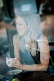 Meisje in het venster van een koffiewinkel die wordt gezeten Stock Afbeeldingen