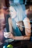Meisje in het venster van een koffiewinkel die wordt gezeten Stock Foto's