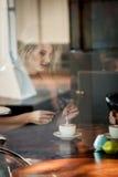 Meisje in het venster van een koffiewinkel die wordt gezeten Stock Fotografie