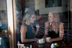 Meisje in het venster van een koffiewinkel die wordt gezeten Royalty-vrije Stock Foto's