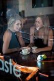 Meisje in het venster van een koffiewinkel die wordt gezeten Stock Afbeelding