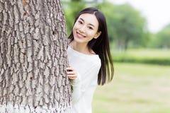 Meisje het verbergen achter de bomen Royalty-vrije Stock Foto's