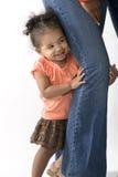 Meisje het verbergen achter de veiligheid van haar moedersbeen stock foto