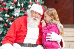 Meisje het Vertellen Wens in het Oor van de Kerstman Stock Afbeeldingen