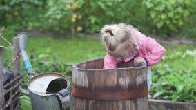 Meisje het water geven aardbeien in de tuin stock video