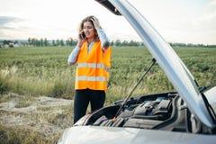Meisje in het wijzen van op vest met telefoon, gebroken auto Royalty-vrije Stock Fotografie