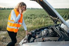 Meisje in het wijzen van op vest met telefoon, gebroken auto stock fotografie