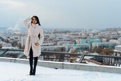 Meisje in het witte bontjas stellen tegen de achtergrond van de stad Royalty-vrije Stock Foto's