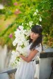 Meisje in het witte kleding stellen met mooie witte bloemen royalty-vrije stock afbeeldingen