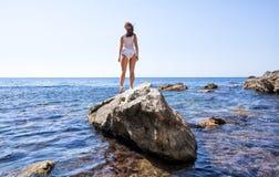 Meisje in het witte lingerie stellen terug op rots royalty-vrije stock afbeelding