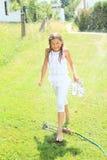 Meisje in het witte lopen door sproeier Royalty-vrije Stock Foto's