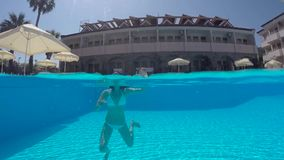 Meisje in het witte zwempak zwemmen onderwater in de pool stock videobeelden