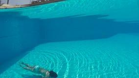 Meisje in het witte zwempak zwemmen onderwater in de pool stock footage