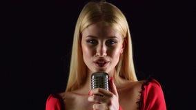 Meisje in het zingen in retro microfoon dolkomisch lied Zwarte achtergrond stock video