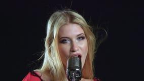 Meisje in het zingen in retro microfoon dolkomisch lied Zwarte achtergrond Sluit omhoog stock video