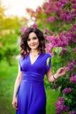 Meisje in het zonlicht naast lilac Bush Stock Fotografie