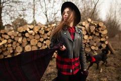Meisje in het zwarte hoed stellen tegen de achtergrond van een brandhout en haar hond stock foto's