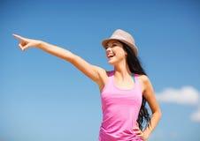 Meisje in hoed die richting op het strand tonen royalty-vrije stock afbeelding