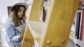 Meisje in hoed het letten op boeken op planken in bibliotheek stock footage
