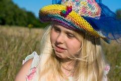 Meisje in hoed op weide royalty-vrije stock afbeelding