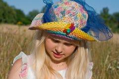 Meisje in hoed op weide stock afbeelding