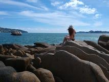 Meisje in hoedenzitting op Acapulco-baairotsen royalty-vrije stock afbeelding