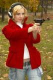 Meisje in hoofdtelefoons met pistool Stock Fotografie