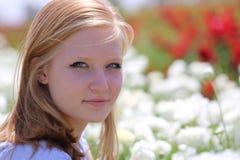 Meisje 16 jaar oud, blonde, op het gebied, onder witte bloemen Stock Fotografie