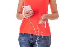 Meisje in jeans en een rode T-shirt met een smartphone met witte hoofdtelefoons stock afbeelding