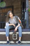 Meisje in jeans, overhemd en sweatshirtzitting op een grote borstaga stock foto's