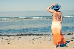 Meisje jonge status die het overzees met de achter achtermening van de strandhoed bekijken stock afbeeldingen