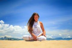 meisje in kant in de lotusbloem van yogaasana op strand tegen blauwe hemel stock foto's
