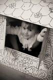 Meisje in kartonhuis Stock Foto's