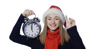 Meisje in Kerstmanhoed met wekker tellende vingers stock video
