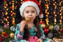 Meisje in Kerstmisdecoratie met gift, donkere achtergrond met verlichting en boke lichten, het concept van de de wintervakantie Stock Foto's