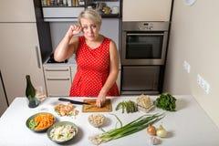 Meisje in keuken scherpe asperge en het wrijven van haar oog Royalty-vrije Stock Foto's