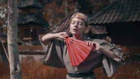 Meisje in kimono met rode handventilator stock footage