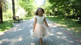 Meisje in kledingslooppas en sprongen in de zomerpark stock video