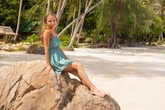 Meisje in kledingszitting op een rots door het overzees stock afbeelding