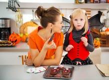 Meisje in knuppelkostuum met moeder die Halloween-koekjes eten Royalty-vrije Stock Foto