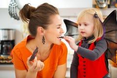 Meisje in knuppelkostuum met moeder die Halloween-koekjes eten Royalty-vrije Stock Afbeeldingen