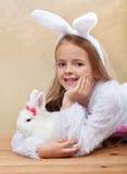 Meisje in konijntjeskostuum holdng haar wit konijn Stock Fotografie