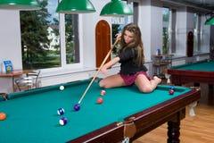 Meisje in korte rok het spelen snooker stock foto