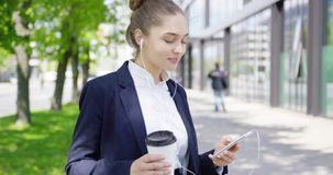 Meisje in kostuum met koffie en smartphone stock videobeelden