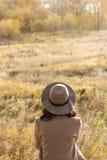 Meisje in laag en hoed die en de afstand zitten onderzoeken royalty-vrije stock fotografie