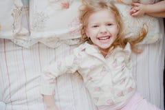 Meisje lachen die op bed liggen stock foto