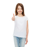 Meisje in lege witte t-shirt die thumbsup tonen stock foto's